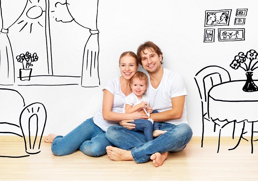 משפחה יושבת מחובקת ומאחוריה ציור של בית